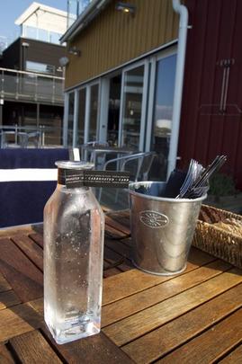 無垢材のテーブル、グラスボトル、ステンレスカップ