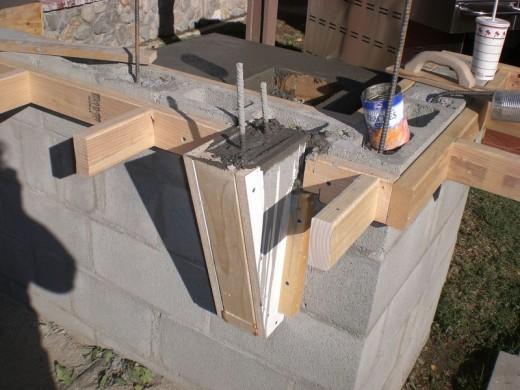 DIYで作った、レンガのカウンターやBBQグリル、シンクのある立派なアウトドアキッチン DIY21カウンタートップの支えのための木枠を取り付けコンクリートを流して鉄筋を