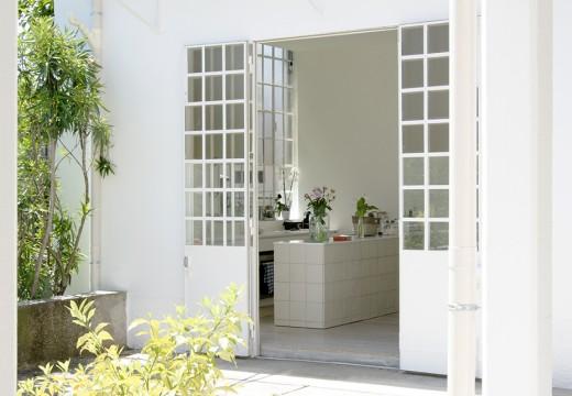 ダイニング・キッチンからベランダの屋外ダイニングにつながる格子窓の入ったフレンチドア
