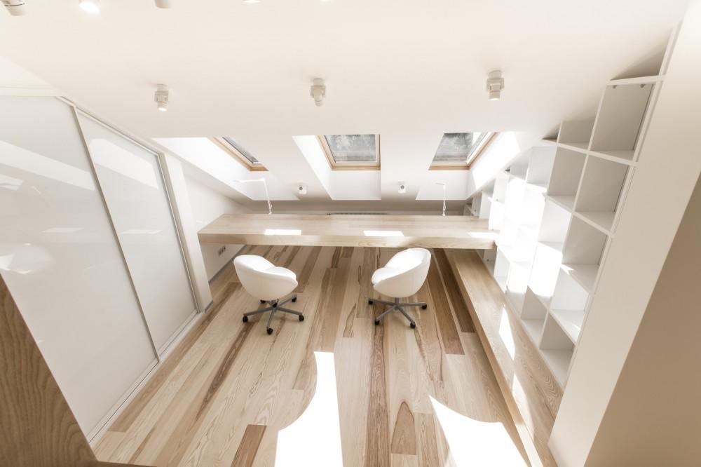 天窓と造作カウンターテーブルのある斜め天井の下のロフトの子供部屋