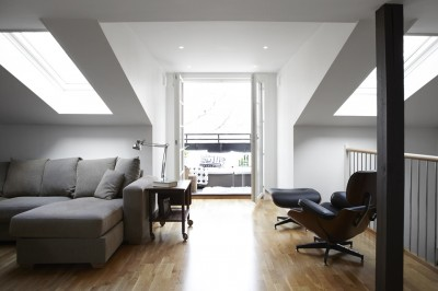 天窓のある低い天井のビリングからテラスの屋外リビングを望む