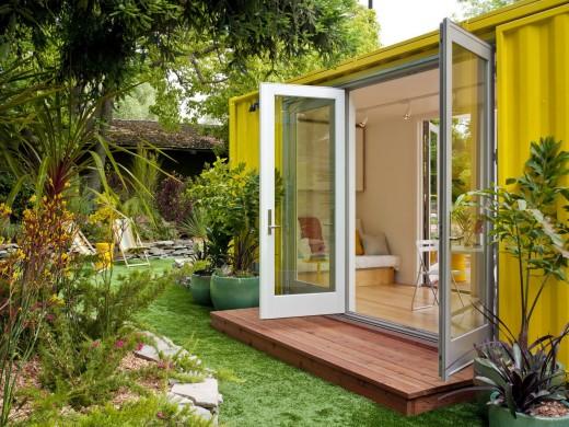 10.7畳のスペースに2つのダブルベッドとリビング、キッチン、バスルームのあるコンテナハウスの裏庭側2