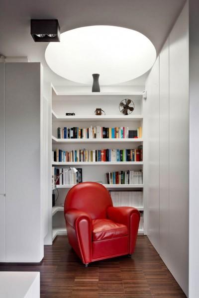 頭上に丸い天窓のある1.5畳程度のコンパクトなリーディングヌック 一人掛けのソファを置いて