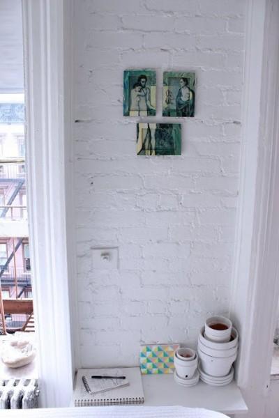 明るく開放的なワンルーム的な部屋のベッドサイドの可愛らしい上げ下げ窓の間の棚のあるスペース