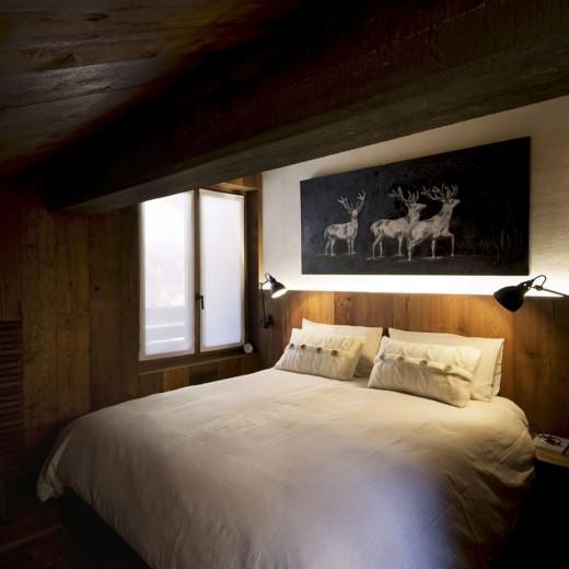 低い勾配天井の下のベッドルーム