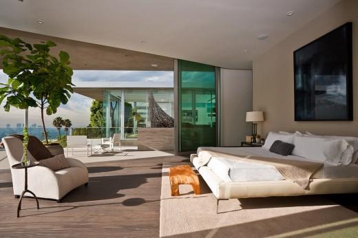 高台に建つ家の開放的な全開口スライドドアのベッドルーム