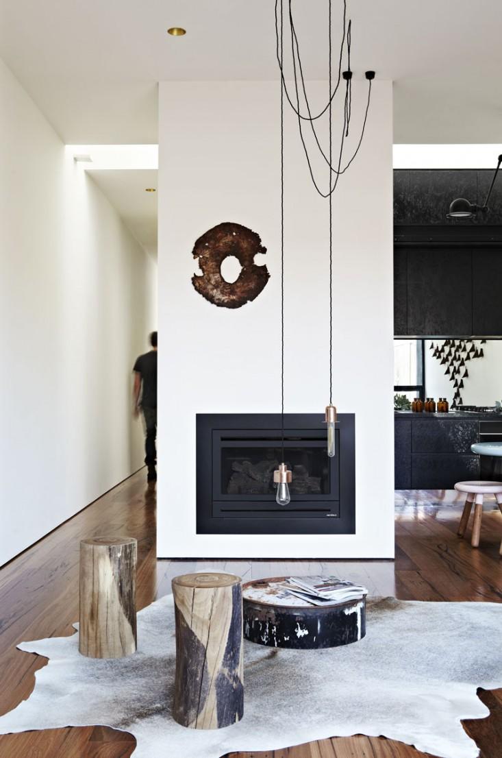天井からシンプルなペンダントライトがぶら下がる暖炉のあるリビング