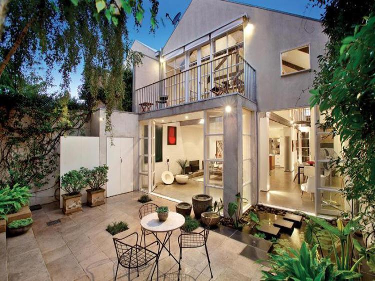 大きく開口する格子入りガラスドアで屋内とフラットにつながる石畳敷きのテラス