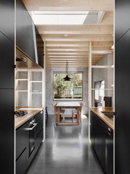 合板製のシンプルで大きな造作棚で周囲を囲われたキッチン