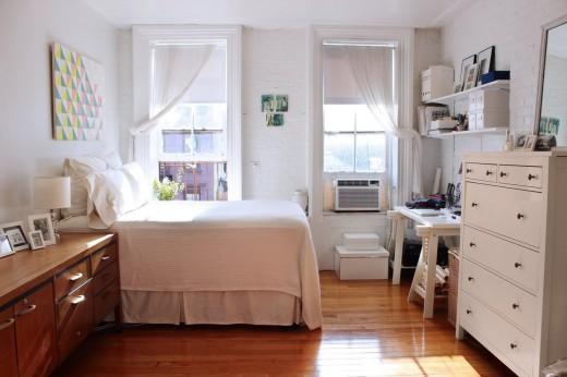 大きな上げ下げ窓が2つ並んだ明るく開放的なワンルーム的な部屋のベッドサイド