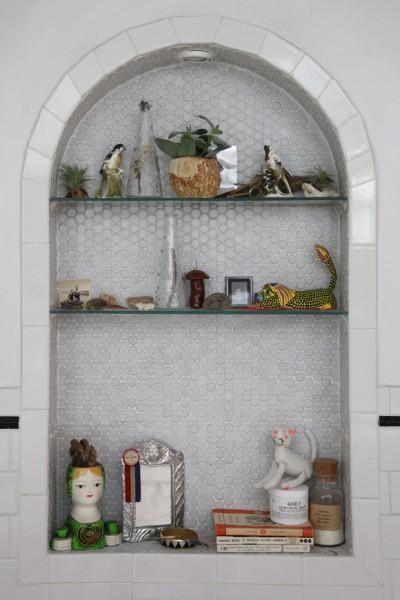 サブウェイタイルと白いペンキ塗りのレンガで囲われたロフトハウスのバスルームの壁に作られたニッチの物置スペース