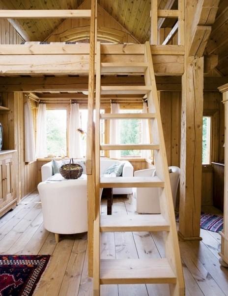 ポーランド スバルキ公園の近くに建つログハウスの、ロフトの下の天井の低いリビングスペースとその上のベッドルーム
