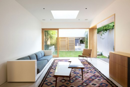ウッドデッキの回廊付きの細長い箱庭住宅のリビング
