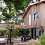 庭の上部にワイヤーを張って頭上をタープで覆ったウッドデッキの屋外リビングスペース