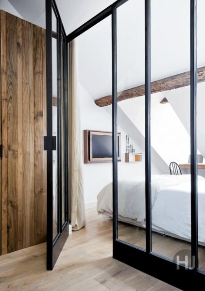 ガラスの壁とドアで仕切られた勾配天井下のベッドルーム1