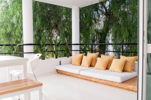 広く明るく開放的なベランダに作り込まれた屋外リビング・ダイニング 低いソファを置いて