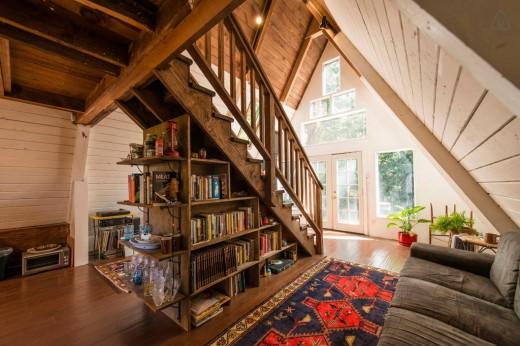 森の中に建つコンパクトなAフレームの山小屋 玄関から入ったところ 中央に階段、その下は本棚と収納棚