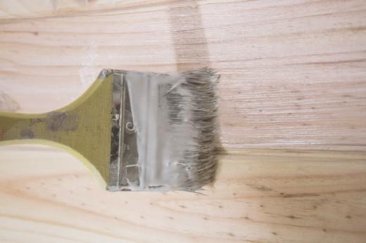 壁に打ち付けた横木をニスやオイルステインで仕上げる
