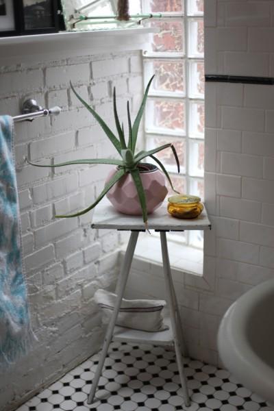 サブウェイタイルと白いペンキ塗りのレンガで囲われたロフトハウスのバスルームのコーナーのガラスブロックの小窓