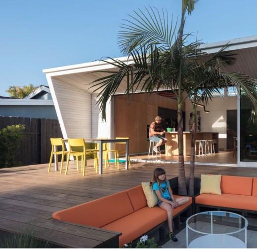屋内とシームレスにつながるウッドデッキのテラスの屋外ダイニングと掘りごたつ的に1段低い屋外リビングスペース