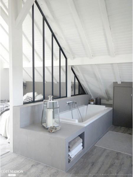 ガラスの間仕切り壁でベッドルームとしきられた勾配天井の下のバスルーム