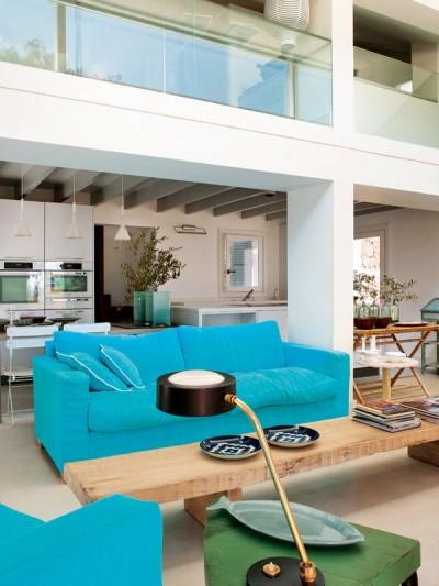 シンプルな内装にカラフルな色使いの家具を配した吹き抜けのあるリビング2