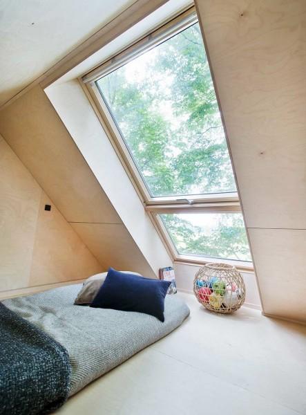 大きな天窓のある勾配天井の下のロフトのベッドルーム