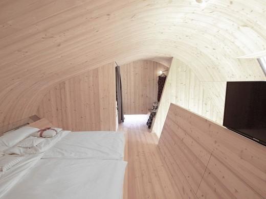 天井がドーム状にカーブした板張りのベッドルーム1