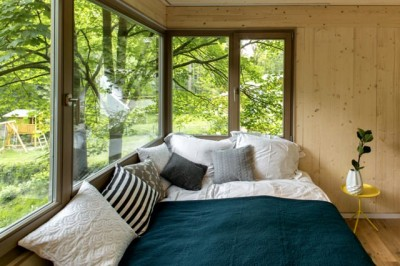 森のなかに建つツリーハウスの窓際の開放的なベッド