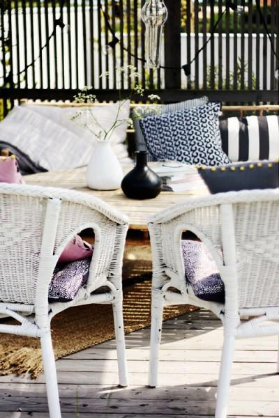 バンブーのソファと白いラタンのチェアのあるウッドデッキの屋外リビング