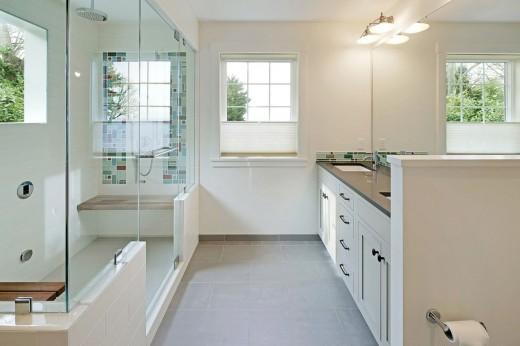 ガラスの壁で囲われた明るく開放的なシャワーブースとその脇の洗面エリア