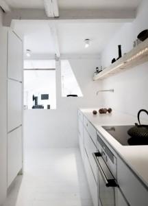 真っ白なキッチンの中で混ざり合う照明の灯りと日光