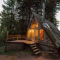 森の中に建つコンパクトなAフレームの山小屋の外観 夕暮れ