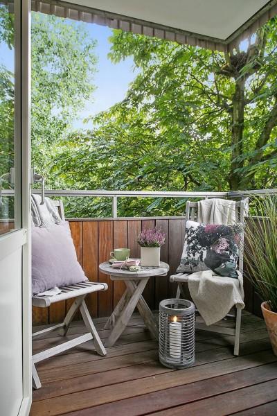屋外家具のチェアとテーブルとキャンドルのある、リビングに隣接するベランダの屋外リビング