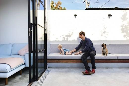 大きなガラスのスライドドアで屋内とつながる、リビング脇の屋外リビング 造作ベンチ付
