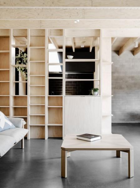 合板製のシンプルで大きな造作棚のあるキッチンの隣のリビング