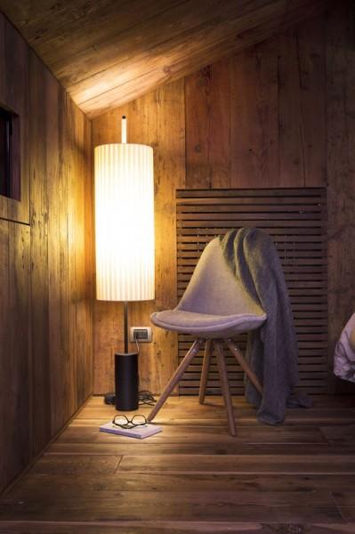 低い勾配天井の下のベッドルームのコーナーに座り心地の良さそうな椅子を置いた寛ぎのスペース
