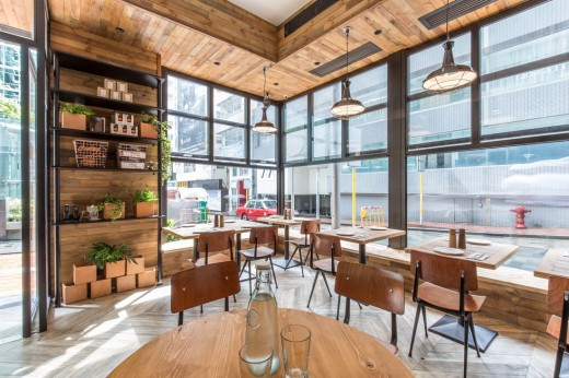 壁際に縁側的なベンチシートのある開放的なカフェのダイニング 室内から窓 縁台側をのぞむ