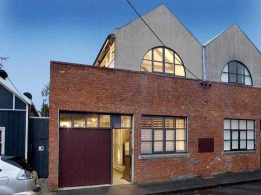 大きく開口する格子入りガラスドアで屋内とフラットにつながる石畳敷きのテラスのある家の外観