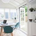 丸テーブルと天窓のある、天井の低い正方形のダイニングルーム