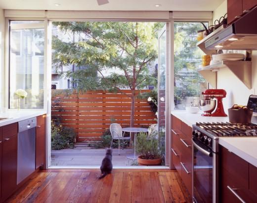 庭との間がサイドまでガラス張りになった大開口のガラスドアでつながる明るく開放的なキッチン