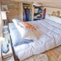 低く緩やかな勾配天井の下の大きな窓のあるロフトベッドルーム