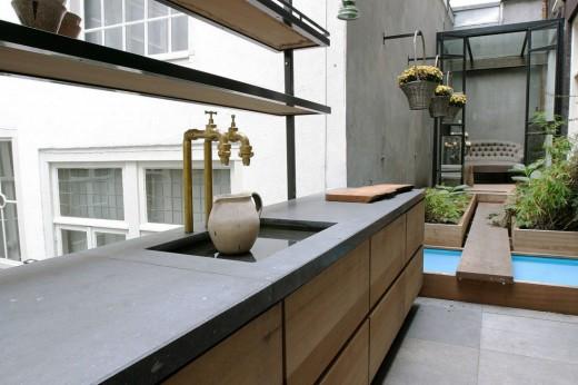ガラス張りの温室の屋外リビングと流しのあるテラス
