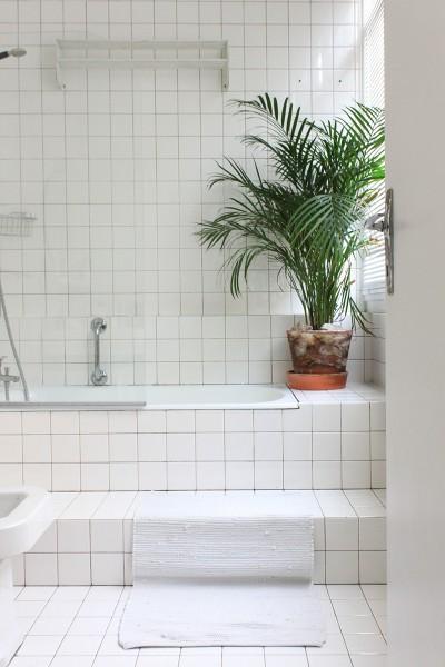 白いタイル貼りの明るく開放的な白基調のバスルーム 段差あり