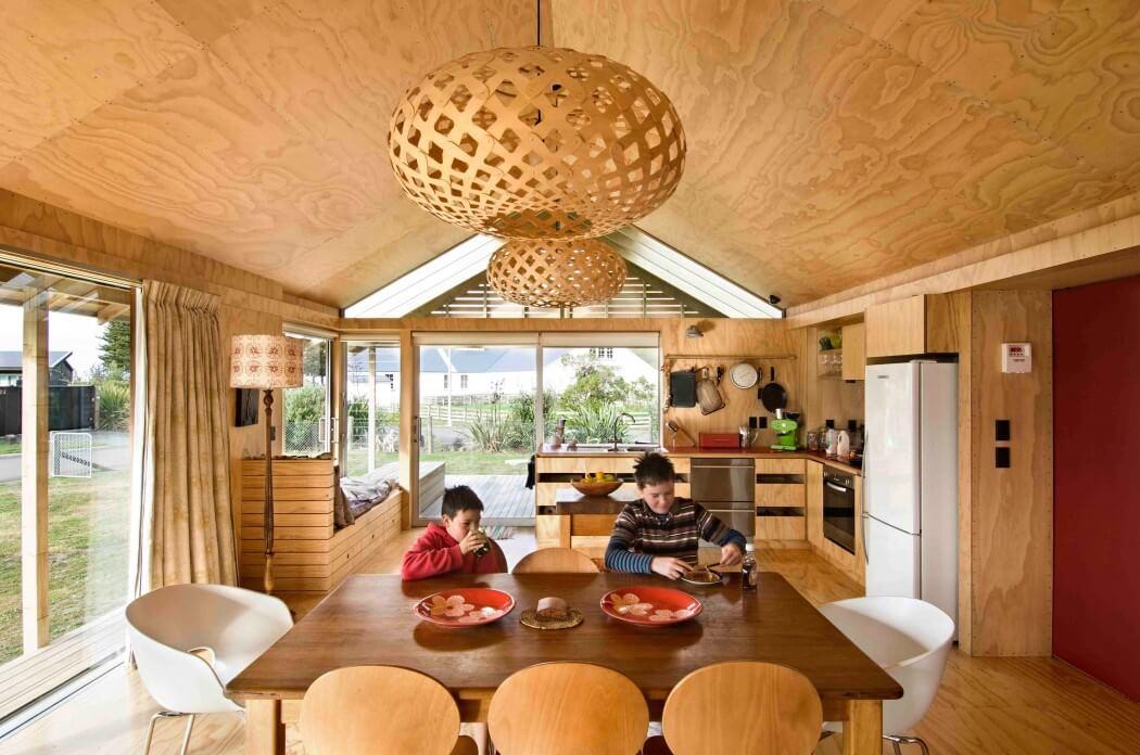 ウッドデッキのテラスと2つのデイベッドスペースのある明るく開放的なダイニング・キッチン