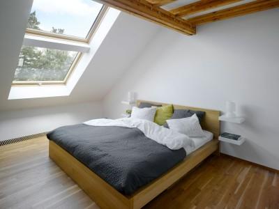 勾配天井の下の大きな天窓が2つあるベッドルーム