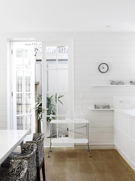 庭につながる格子入りの白いフレンチドアと横張りの白い壁板が可愛らしい開放的なダイニング・キッチン