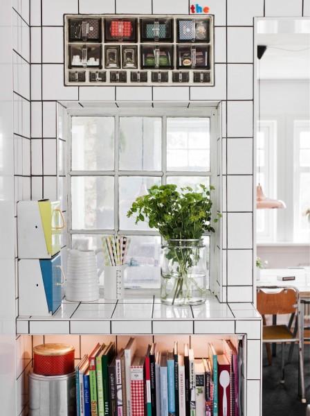 壁全面が白いタイル貼りの白基調のキッチン 室内窓とニッチ状の収納 本棚