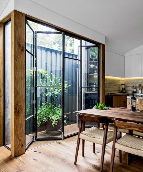 ダイニング・キッチンに隣接する温室のようなコンパクトなウッドデッキのテラス