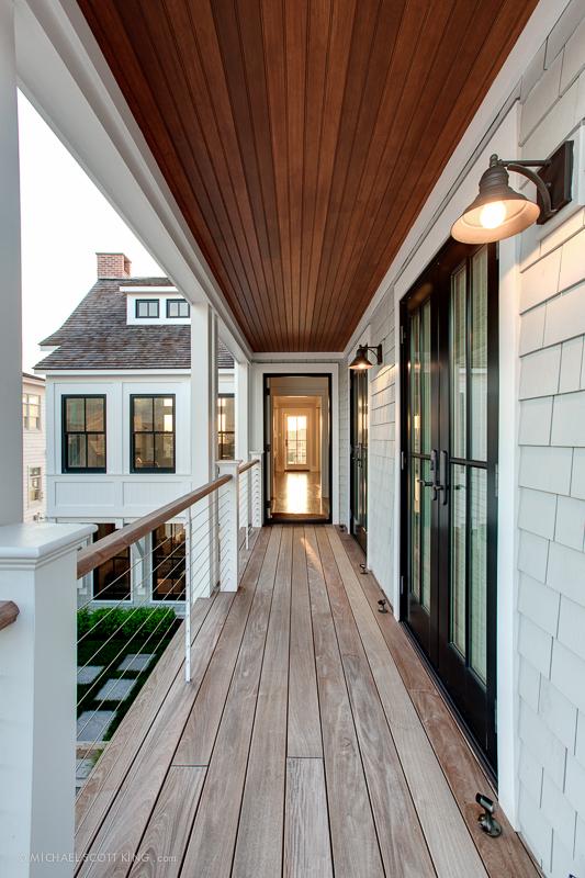 見晴らしの良いバルコニーの屋外リビングにつながるウッドデッキの開放廊下